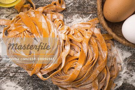 Red pepper, fresh eggs and semolina handmade fettuccine pasta