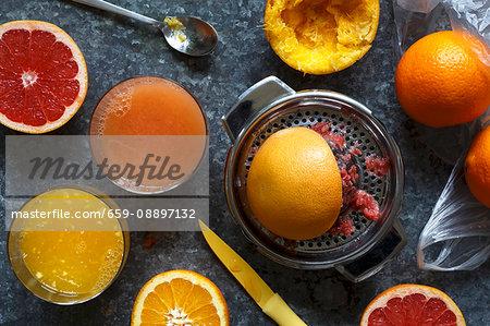 Manual metal citrus fruit extractor next to glasses of orange juice and red grapefruit juice and whole and half cut oranges and red grapefruit