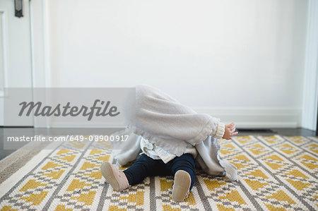 Baby girl hiding under blanket