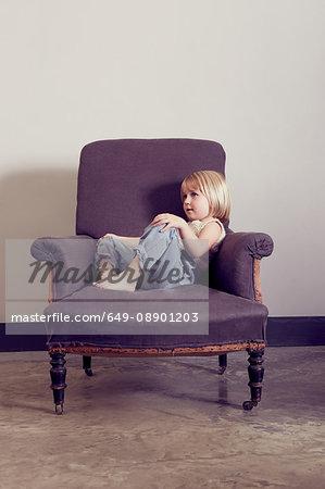 Girl reclining on vintage armchair gazing