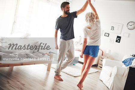 Couple in bedroom, wearing pyjamas, dancing
