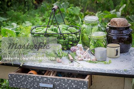 Freshly pickled gherkins in preserving jars on a garden table