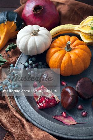 An autumnal arrangement of pumpkins, chestnuts, pomegranates and berries