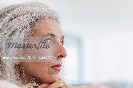 Close up serious, pensive mature woman looking away