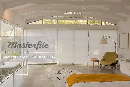 Modern, minimalist bedroom with vaulted wood beam ceiling