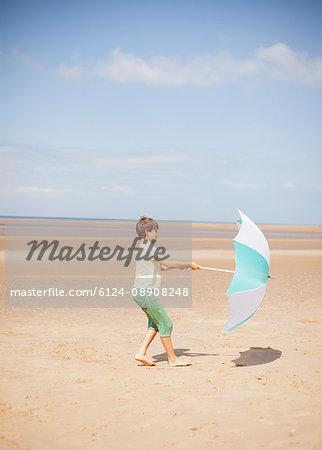 Wind pulling umbrella in hands of boy on sunny summer beach