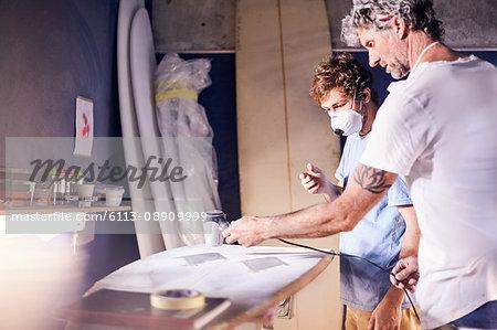 Male surfboard designers wearing protective masks sanding surfboard in workshop