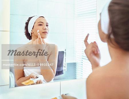 Woman applying moisturizer to cheek at bathroom mirror