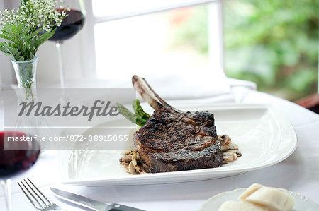 Bone in rib eye steak served on white oval plate, Club Continental, Orange Park, FL.