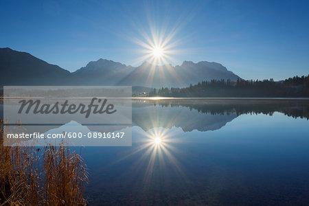 Karwendel Mountains backlit against the bright sun reflected in Lake Barmsee at Kruen in Upper Bavaria, Germany