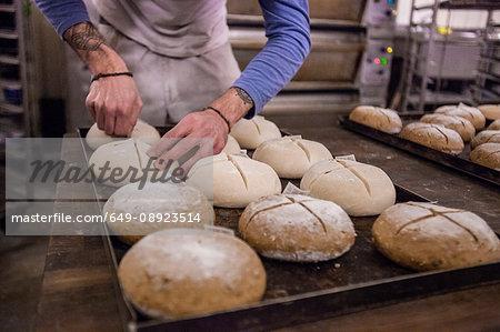 Baker scoring dough in bakery