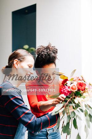 Florist and student arranging bouquet at flower arranging workshop