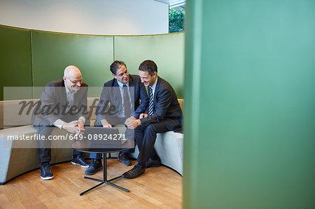 Three businessmen meeting on office sofa