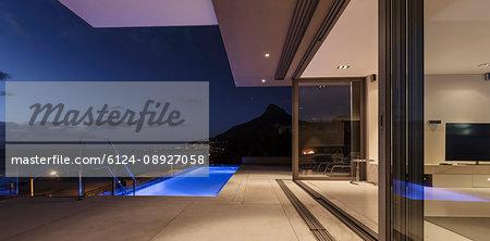 Illuminated blue lap swimming pool outside modern luxury home showcase exterior at night