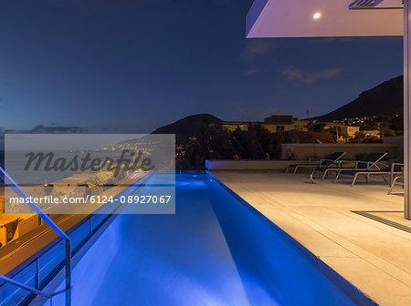 Illuminated blue lap swimming pool on luxury patio at night