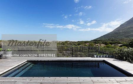 Tranquil dark swimming pool under sunny blue sky