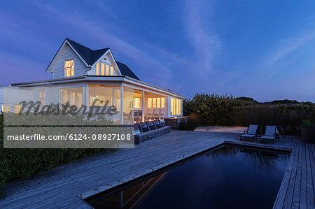 Illuminated white home showcase exterior and swimming pool at night