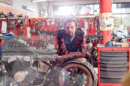 Portrait serious, confident motorcycle mechanic in workshop