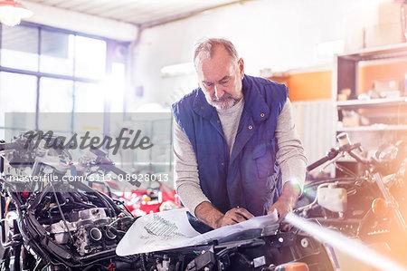 Senior male motorcycle mechanic reviewing plans in workshop