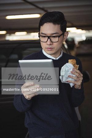 Man using digital tablet while eating snack in garage