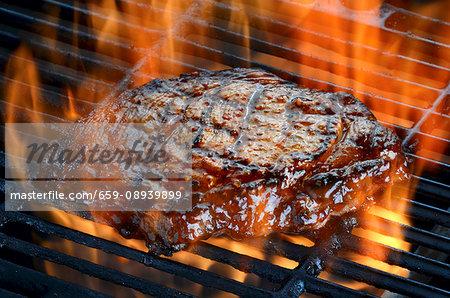 A ribeye steak on a flaming barbecue