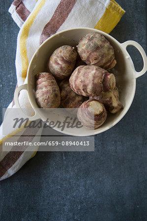 Fresh Jerusalem artichokes in a colander on a tea towel
