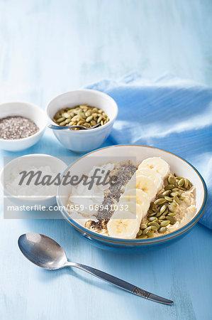 Porridge with bananas, pumpkin seeds, chia seeds and coconut flakes