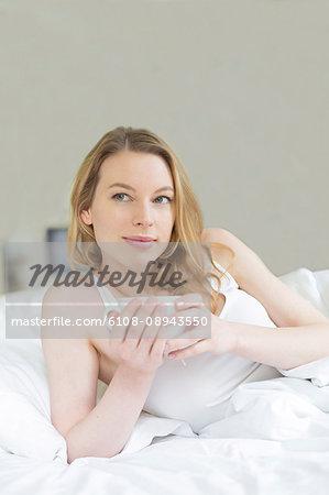 Pretty pensive woman enjoying a tea in bed