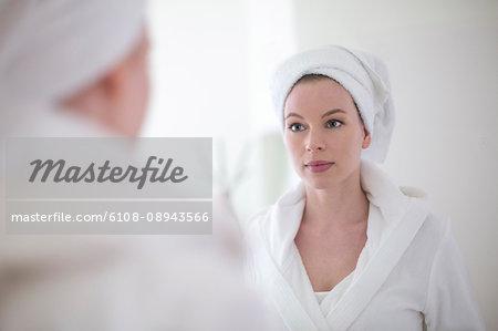 Pretty blonde woman in bathrobe looking herself in the mirror
