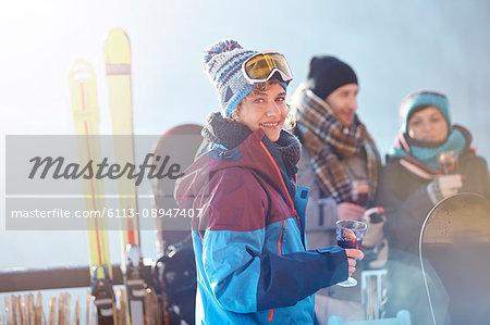 Portrait smiling female skier drinking cocktail on balcony with friends apres-ski