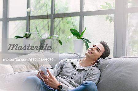 Man wearing headphones sitting on sofa