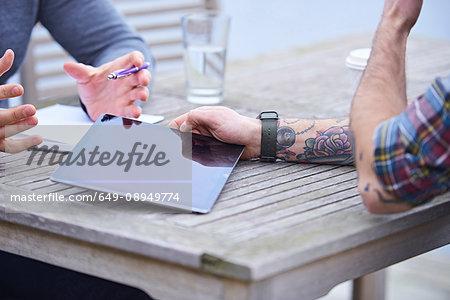 Cropped shot of male design team using digital tablet outside design studio