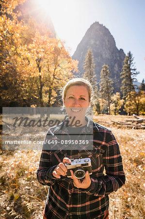Portrait of woman holding camera in autumn landscape, Yosemite National Park, California, USA