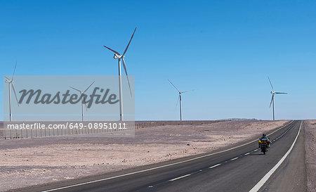 Man on touring motorbike driving past windfarm, Atacama desert, San Pedro de Atacama, Antofagasta, Chile, South America
