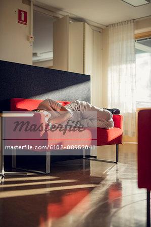 Female doctor sleeping on sofa