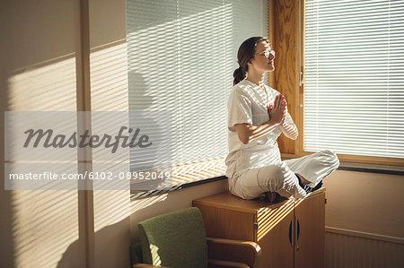 Female doctor meditating by window