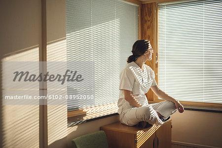 Female doctor sitting by window