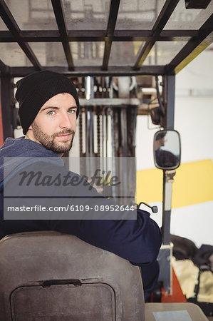 Portrait of mechanic sitting on forklift