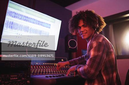 Portrait of male audio engineer using sound mixer in recording studio