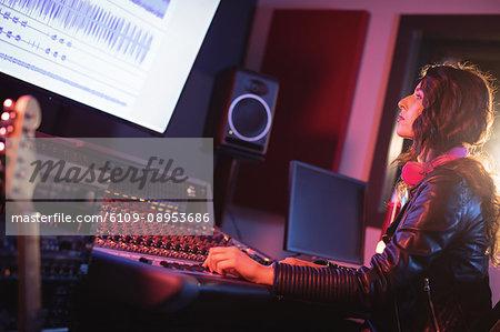 Female audio engineer using sound mixer in recording studio