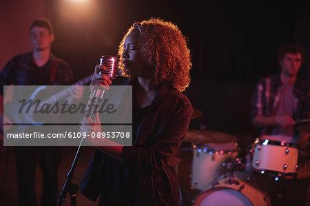 Woman singing on retro microphone in recording studio