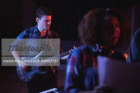 Musician playing electronic guitar in recording studio