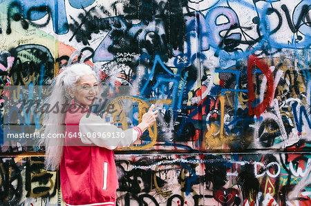 Portrait of mature woman in baseball jacket spray painting graffiti wall