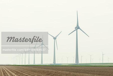 Row of wind turbines in field dyke landscape