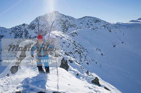 Skier walking on ridge of snow mountain