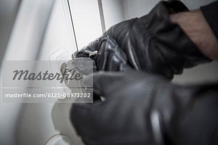 Thief trying to open a door lock