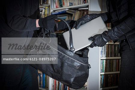 Burglars stealing laptop