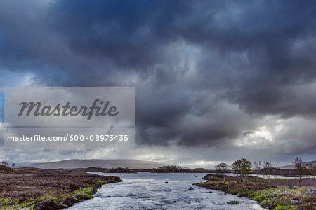 River in moor landscape with dark storm clouds at Rannoch Moor in Scotland, United Kingdom