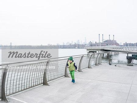 Boy running along waterfront, New York, USA