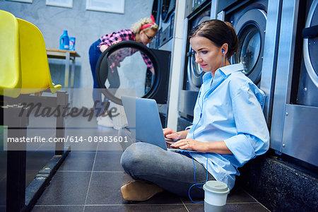 Woman sitting on laundrette floor typing on laptop